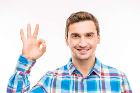 A young smiling man shows gesture OK