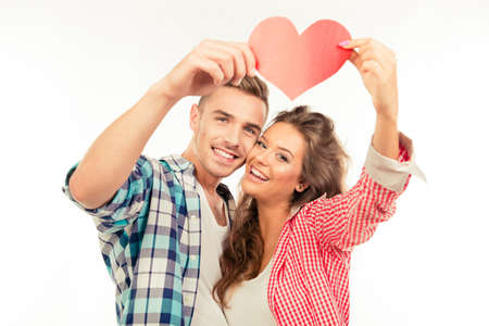 love story: Happy cute couple in love embracing each other holding paper heart Stock Photo