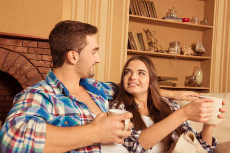 siting: Cute young couple siting together with cups and smiling