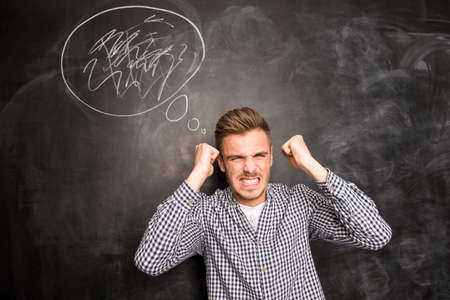 wroth: Angry young man in rage standing against the background of chalkboard Stock Photo