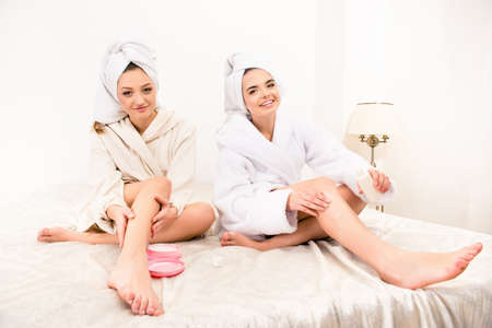 smearing: Nice happy young women smearing cream on their legs