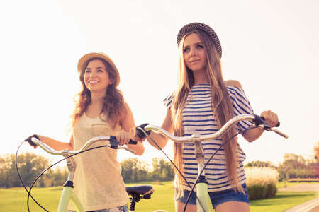 lesbian sexy: cute happy girls with hat ride bicycles on the park Stock Photo