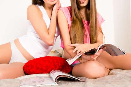pijamada: Closeup photo of girls in pajamas sitting on the bed reading magazines