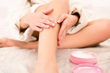 piernas mujer: Foto de detalle de la joven mujer se corra la crema en su pierna