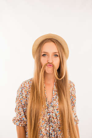 comically: Funny girl joking and making moustache with her hair