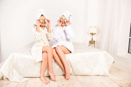 Two funny young women with cucumbers on eyes and towel on their heads