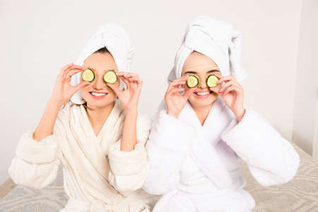 Funny cheerful young women with cucumbers on eyes and towel on their heads