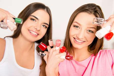 lesbo: Beautiful girls in pajamas holding varnishes
