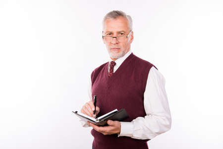 Portrait of old handsome businessman in an elegant suit making notes Stock Photo