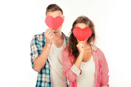 Happy couple in love embracing each other hiding faces behind two paper hearts