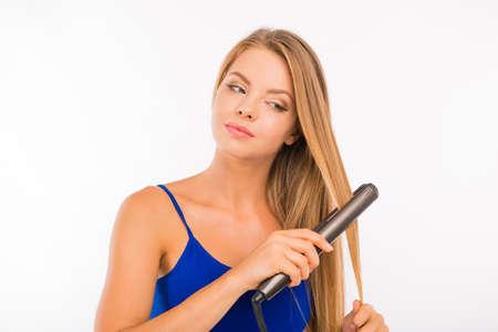 straightener: Beautiful young girl using a straightener