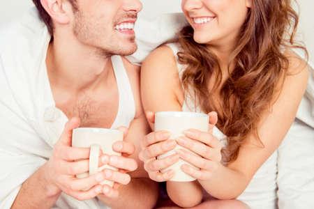 amigos abrazandose: pareja joven linda que se sienta junto con las tazas y sonriente Foto de archivo