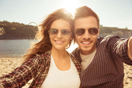 Two lovers making a selfie photo near the river, close-up photo Foto de archivo