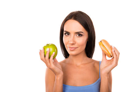 unwholesome: Happy young woman deciding between an apple and burger