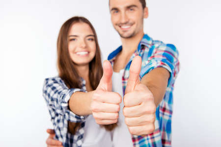 cute love: Happy cute couple in love embracing each other showing thumbs up Stock Photo