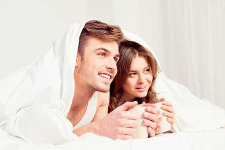 amigos abrazandose: Pareja joven lindo con las tazas y sonr�e bajo la manta