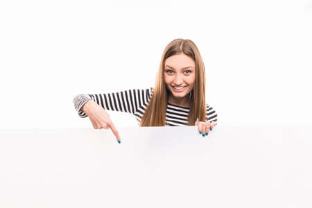 Positive happy girl pointing down to the empty space