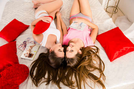 sleepover: Cheerful girls in pajamas gossiping and lying on the bed holding magazines
