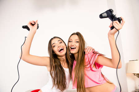 lesbo: Cheerful attractive girls playing video games
