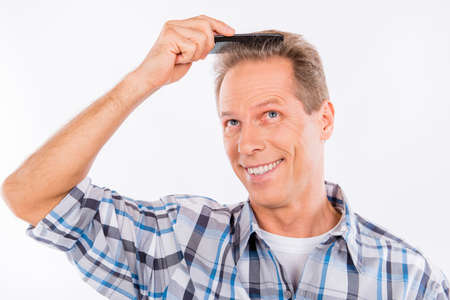 Handsome funny happy aged man combing his hair