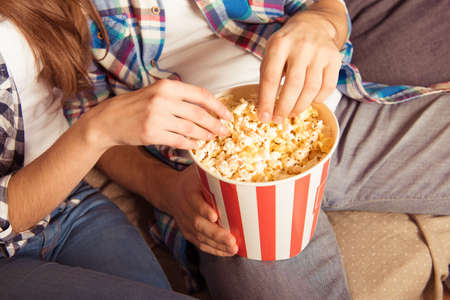 eating popcorn: young woman and man in tartan shirt eating popcorn Stock Photo