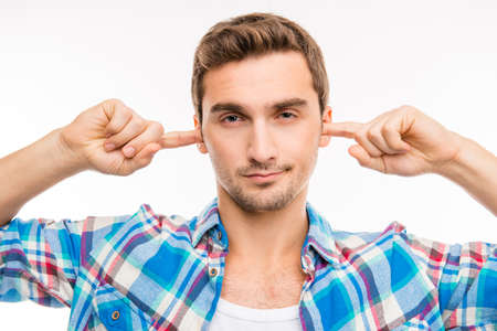 bad temper: Young handsome man covering his ears ignoring noise