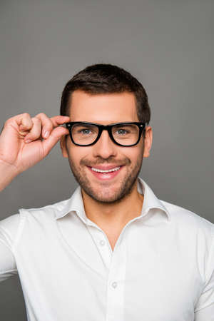 glases: Smart smiling man touching his glases