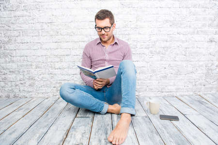 cute guy: Young man in glasses sitting on the floor and reading book