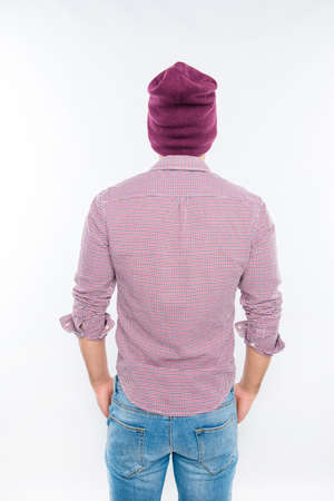 back view of man: Back view photo of modern man in hat holding hands in pockets