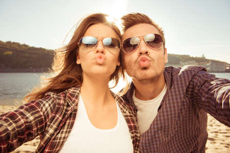 Couple in love making selfie photo at the seaside with kiss, close-up photo Stock Photo