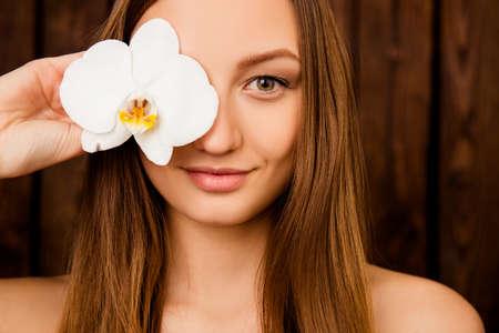 sauna nackt: Close-up-Portr�t von M�dchen eine Orchidee in der N�he ihrer Augen halten