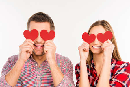 Close up photo of happy couple in love hiding eyes behind paper hearts