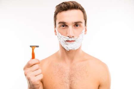 boy  naked: Pretty young man with shaving foam on his cheeks holding a razor