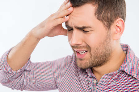 Handsome young man touching his head with one hand feeling strong headache, close up photo