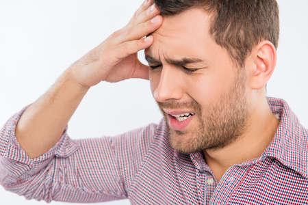 Knappe jonge man te raken zijn hoofd met één hand het gevoel sterk hoofdpijn, close-up foto