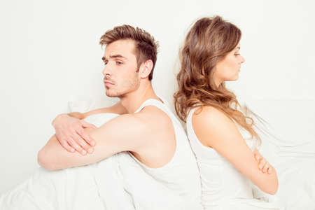 Young disconnected couple with problems sitting on the bed
