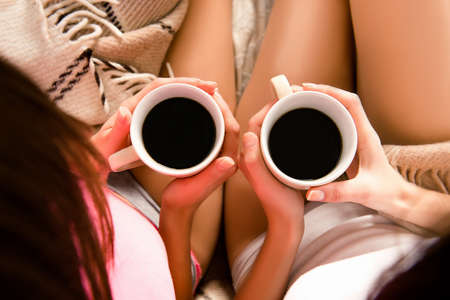 lesbo: Close up photo of two cups of coffee in hands, top view point