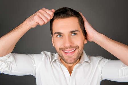 bel homme: Beau jeune homme gai peigner ses cheveux