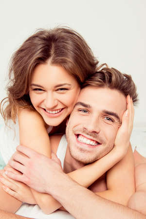 Happy girl in love at home embracing boyfriend Stock Photo