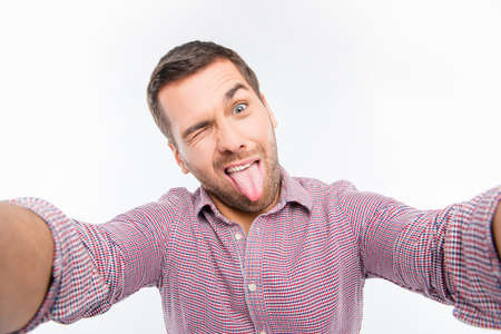 sexy style: Attractive man making comic selfie with tongue