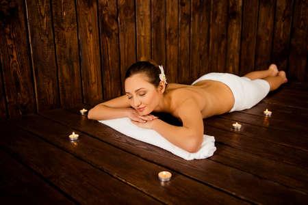 sauna nackt: Mädchen im Spa, auf dem Tisch in ein Handtuch eingewickelt liegen Lizenzfreie Bilder
