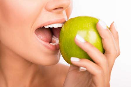 Closeup photo of a beautiful healthy girl biting an apple Stock Photo