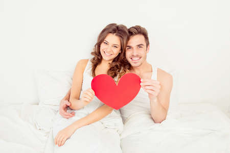 Lovely couple in love holding red paper heart in bed