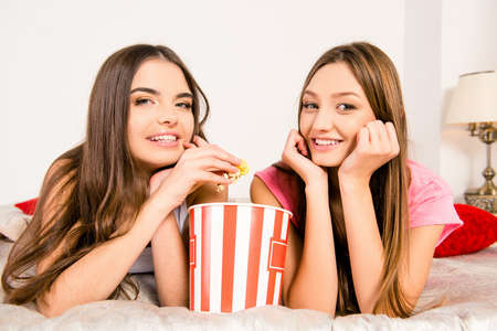 lesbo: Cheerful girls in pajamas sitting in plaid with popcorn