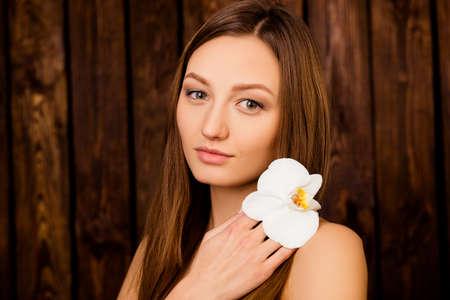 sauna nackt: Portr�t des M�dchens eine Orchidee in der N�he von ihren Schultern halten
