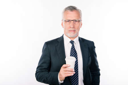 mature business man: Aged handsome man with glasses in a black suit holding a cup of coffee