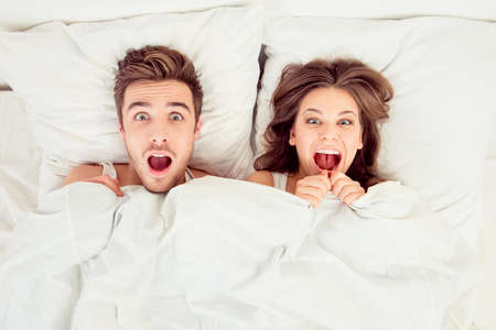 Surprised funny couple in love lying in the bed Standard-Bild