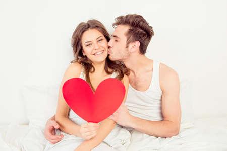 Lovely pareja en el amor la celebración de corazón de papel rojo en la cama y besos