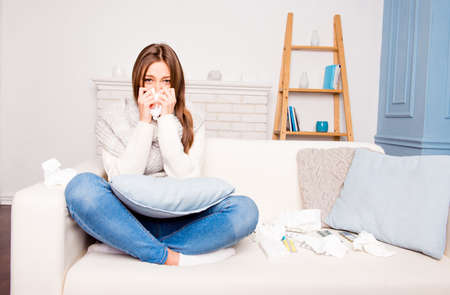 rheum: Sick  girl with fever sneezing in tissue sitting on sofa, close up photo