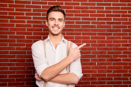 Handsome confident man pointing away, close up photo
